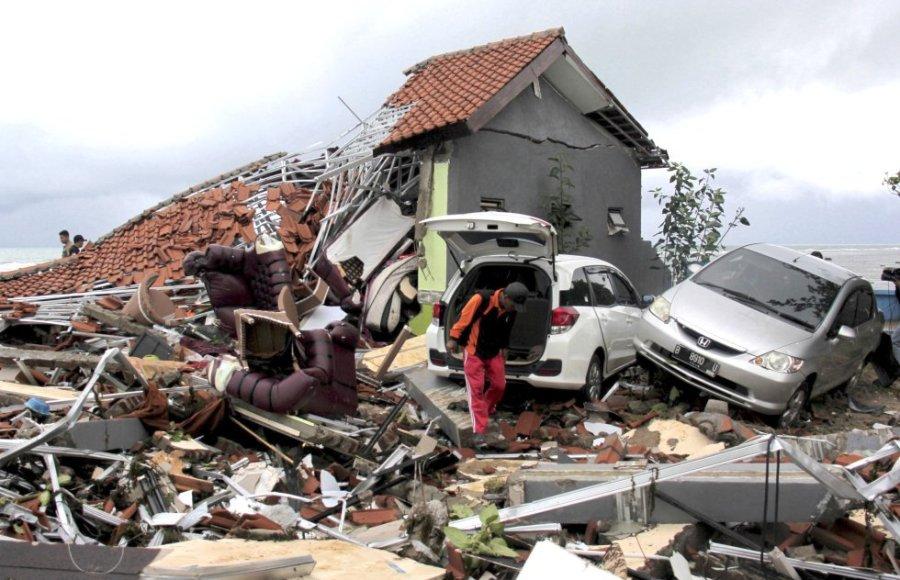 Un hombre junto a los restos de una vivienda destruida tras el paso del tsunami en Anyar (Indonesia).