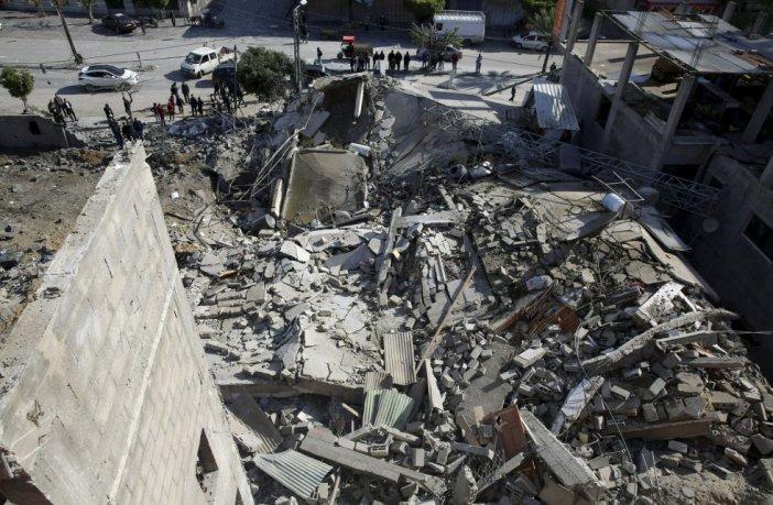 Un grupo de palestinos se reúne frente a los restos de una tienda en Gaza, este martes, tras el bombardeo israelí sobre la ciudad, en respuesta al ataque palestino de este lunes a Moshav Mishmeret (Israel), con un saldo de siete personas heridas.