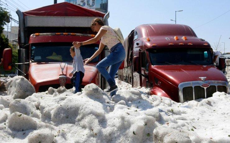 El granizo afectó a decenas de vehículos en Guadalajara, capital del estado de Jalisco, y dejó sepultados numerosos coches. En la imagen, una mujer camina junto a su hijo sobre una montaña de granizo.