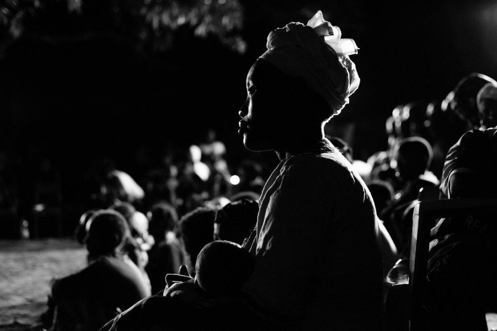 La asistencia a la obra de teatro en la localidad de Flabougoula ha sido muy numerosa, las mujeres han llegado cargadas con sillas y la mayoría de ellas con sus bebés a cuestas. En la imagen, se ve cómo una mujer amamanta a su bebé mientras atiende a la representación en la aldea de Flabougoula.
