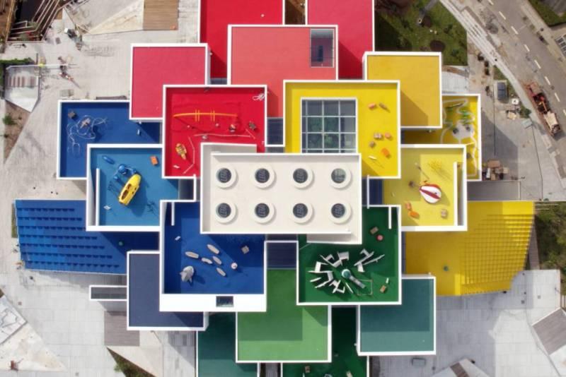 Bjarke Ingels, el arquitecto danés fundador del estudio BIG, es el autor de la nueva Lego House (Casa Lego), en Billund (Dinamarca), que hoy se abre al público. Ingels pensó su proyecto para que se pudiera ver desde un helicóptero (y que en Google Earth fuera una referencia inconfundible la perspectiva de terrazas que semejan los ladrillos de colores que fabrica la firma de juguetes de construcción). Las fachadas están recubiertas de azulejos blancos y las azoteas de brillantes colores. En los 21 bloques se desarrollarán actividades para niños y adultos. El espacio interior incluye una zona de exposición, áreas para construir con los bloques de plástico de Lego, un árbol levantado con 6.316.611 piezas, una galería con varios dinosaurios Lego multicolores de gran tamaño y otras esculturas, y un museo sobre la historia de la empresa, fundada en 1932. La entrada completa cuesta 26,75 euros (la plaza, el parque infantil, nueve terrazas y la zona hostelera y comercial son de entrada libre). El museo se une al cercano parque temático de la firma, que ofrece atracciones inspiradas en el mundo Lego.