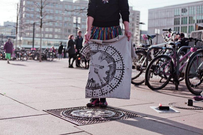 Emma France Raff, cujo nome artístico é Raubdruckerin (algo como a impressora furtiva), vive em Berlim. Cria camisetas, camisolas, sacolas de teia e pôsteres nos quais imprime relevos de calçadas, ruas ou tampas de bueiro das cidades pelas quais viaja. As coleções são pequenas, de poucas peças, exceto no caso dos artigos feitos na capital alemã, onde a artista tem sua oficina ( raubdruckerin.de ),  aberta ao público. Além de em seu site, ali podem ser compradas suas produções, sem dúvida um 'souvenir' único e muito original.