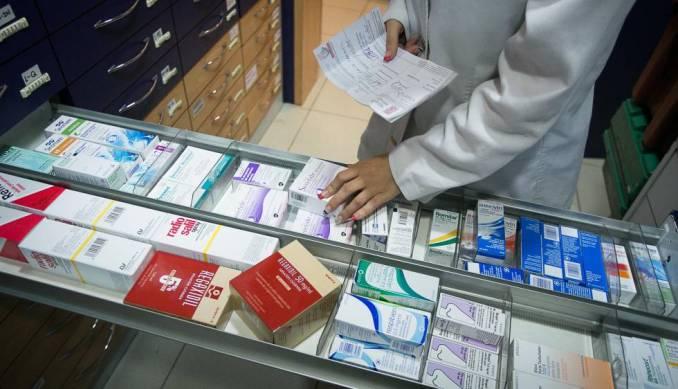 Una farmacéutica busca un medicamento en una estantería