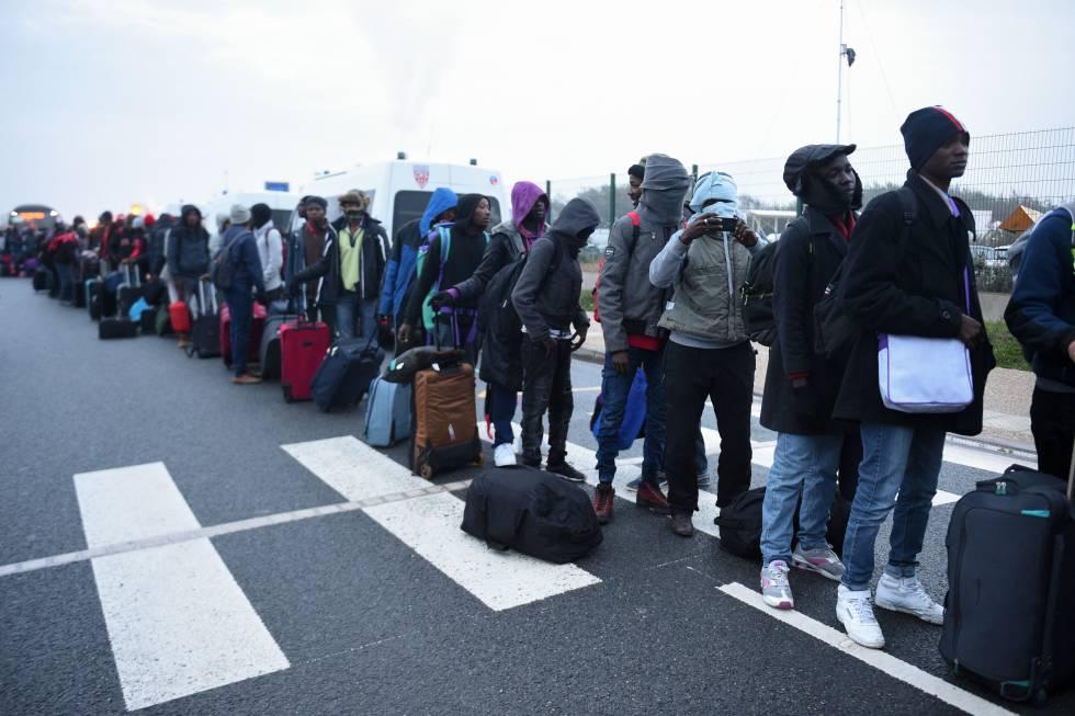 Fila de refugiados esperando ser evacuados del campamento de Calais, en octubre de 2016.