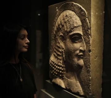 Una mujer contempla el relieve de un oficial del rey asirio Asurbanipal, en la muestra de Londres.
