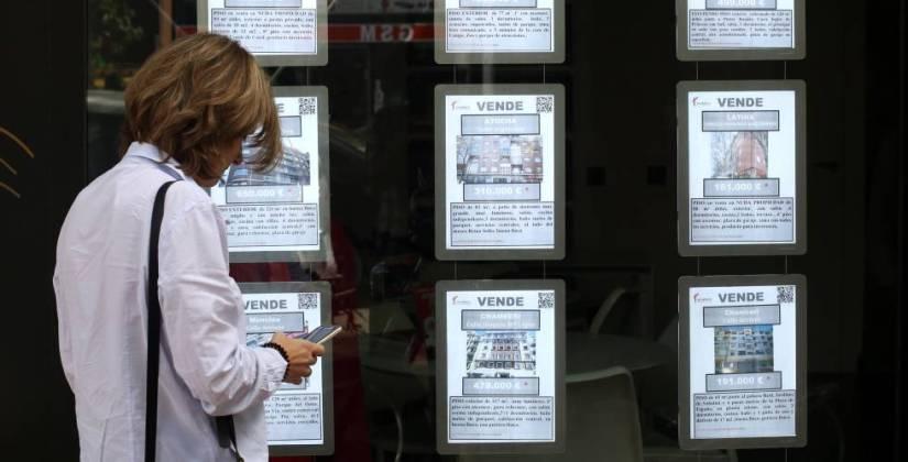 Una mujer apunta en su teléfono móvil frente a una inmobiliaria en Madrid.