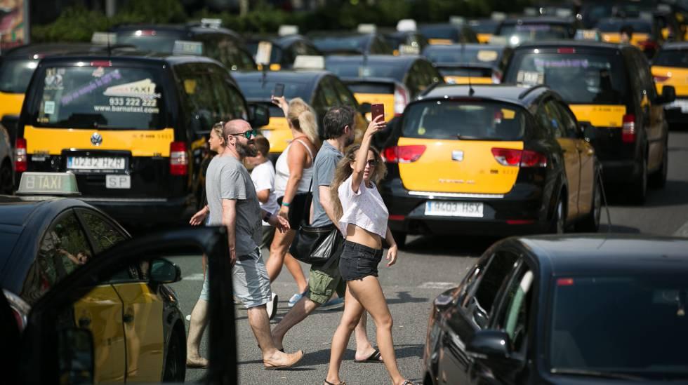 Turistas pasean por la Gran Vía de Barcelona,entre taxistas.