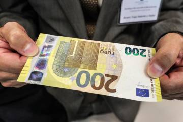 Un periodista sostiene el nuevo billete de 200 euros este jueves durante su presentación en la sede del Banco Central Europeo (BCE) en Fráncfort (Alemania).