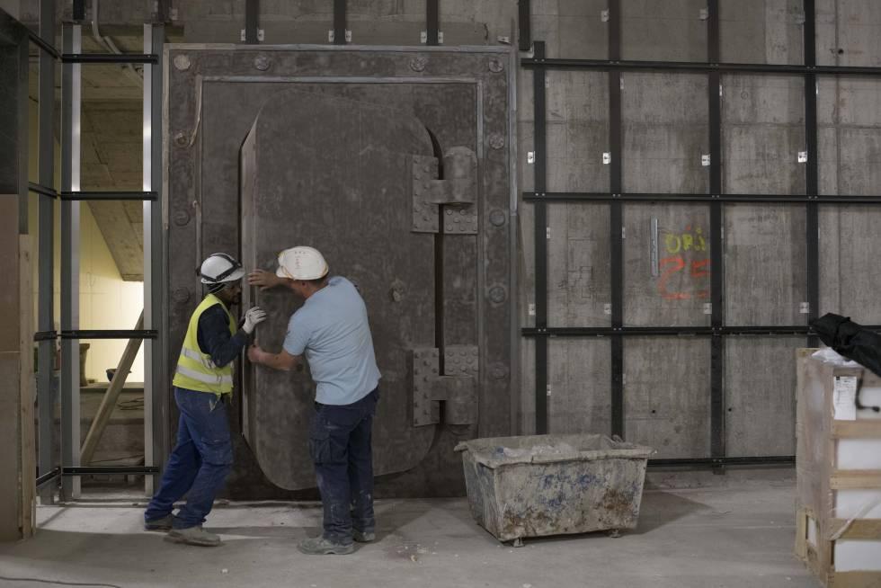 Dos trabajadores abren la antigua caja fuerte de Banesto, ahora en la galería comercial.