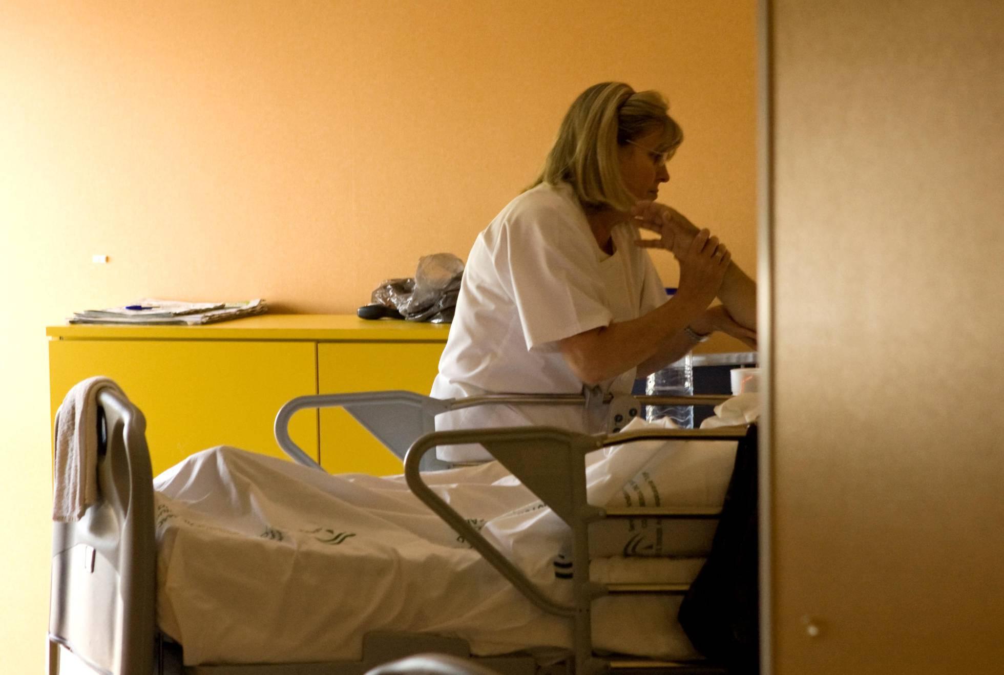 Una enfermera atiende a un paciente en la unidad de cuidados paliativos. EL PAIS