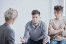 Una persona neutral escucha con atención a una pareja en una sesión de mediación.