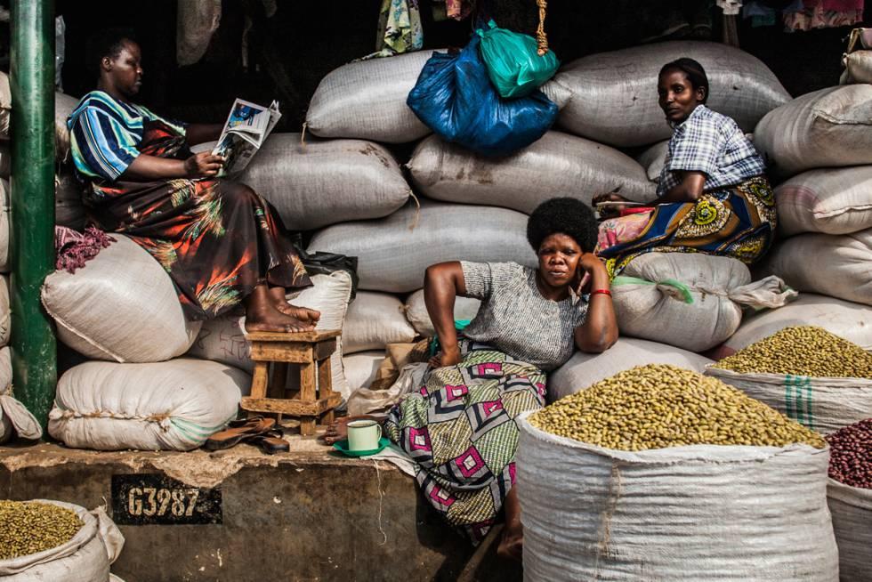 Tres señoras decansan en su puesto de venta de legumbres en Owino Market, Kampala (Uganda), en una imagen de Quico García.