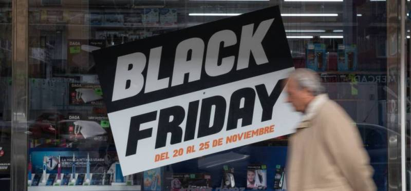 Un señor pasa por delante de un cartel que anuncia ofertas del 'Black Friday' en Madrid.