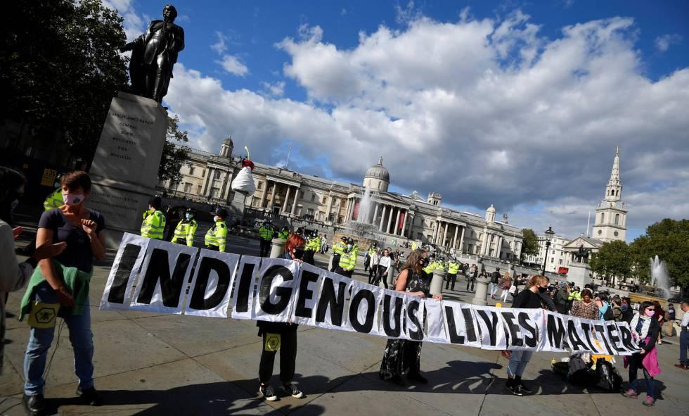 Unos activistas por el clima de la asociación Extinction Rebellion sostienen una pancarta con el lema 'Las vidas indígenas importan' durante una protesta para visibilizar la situación de los pueblos originarios en la Amazonia en la plaza Trafalgar de Londres, Reino Unido, el 5 de septiembre de 2020.