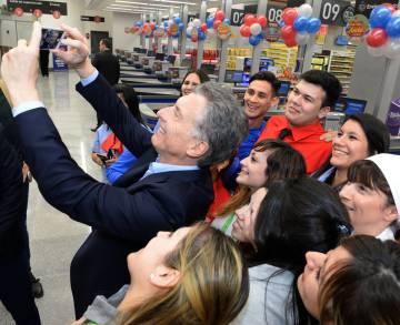 Macri se fotografía con empleados de un nuevo supermercado.