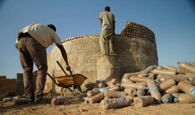 Dos hombres trabajan en la construcción de una vivienda hecha con botellas de plástico en el campamento de Tinduf.