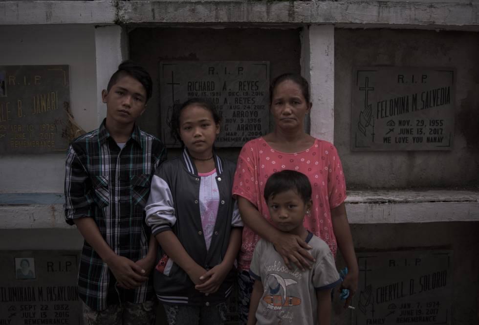 Teresita Yabut e seus filhos diante do túmulo de seu esposo.