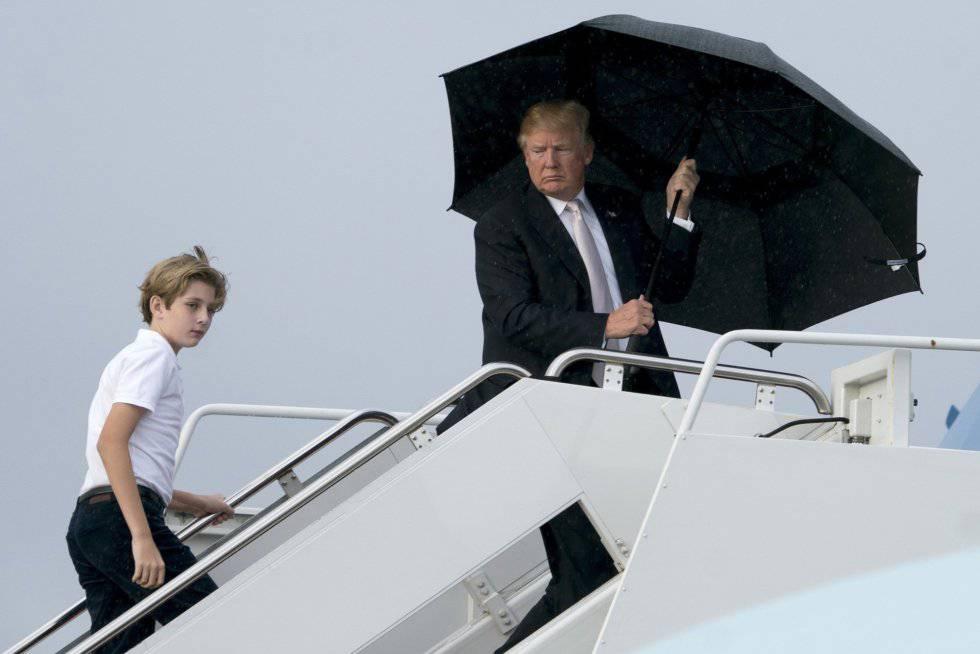 Donald Trump se cubre con un paraguas mientras se mojan su esposa y su hijo menor