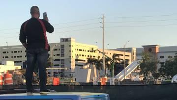 Un hombre toma una foto del puente derrumbado.