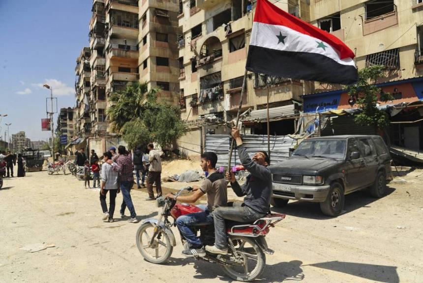 Dos jóvenes ondean una bandera siria en Duma, en las afueras de Damasco.