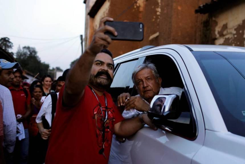 López Obrador se toma una foto con un simpatizante en Michoacán.