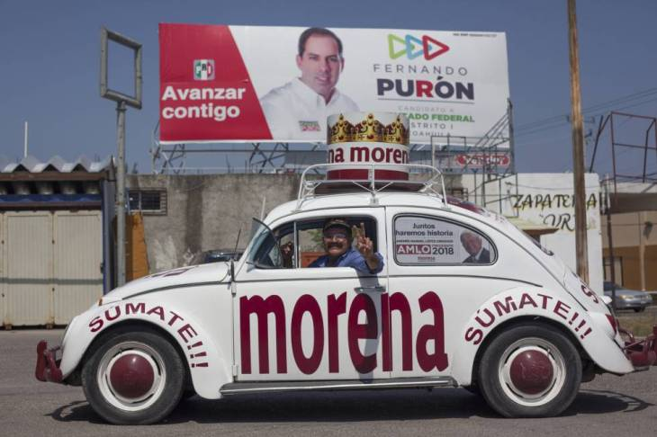 Arturo Cervera junto a su negocio en Piedras Negras. De fondo, propaganda del PRI.