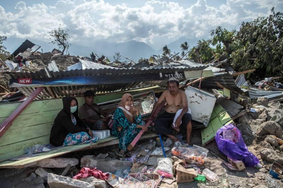 Unos supervivientes, se cobijan en las ruinas de una casa, en Palu.