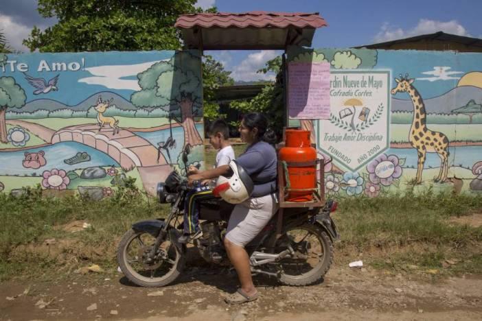 Maribel, con su hijo en su motocicleta durante su jornada de trabajo vendiendo gas.