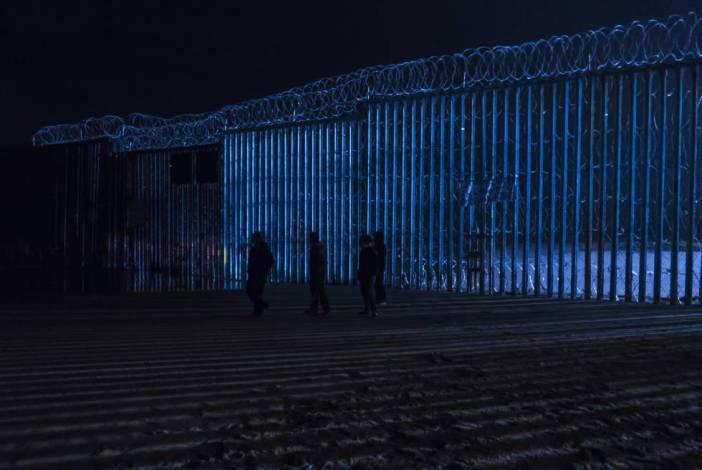 Un grupo de personas camina frente al muro fronterizo de Tijuana, el pasado viernes por la noche.