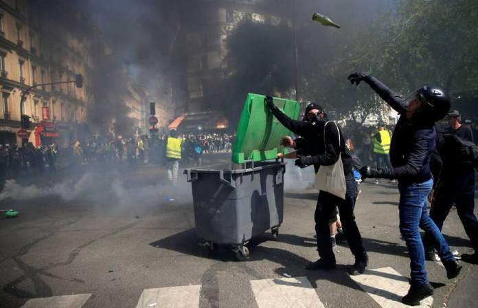 Un manifestante con casco lanza una botella de vidrio, durante los disturbios de este sábado en París.