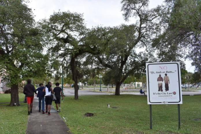 Un grupo de jóvenes pasea cerca de un cartel de prohibición de pantalones caídos en Opa-locka (Florida).