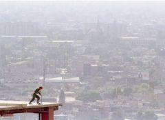 Un trabajador de la construcción en la parte superior de un edificio. Al fondo la nube contaminante / REUTERS