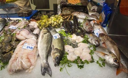 Lubinas, besugos, ostras y otros pescados y mariscos a la venta en un puesto del mercado de Vitoria