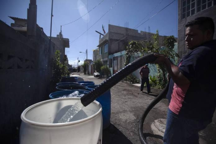 Un hombre rellena un contenedor para almacenar agua en la Alcaldía de Iztapalapa en la Ciudad de México.