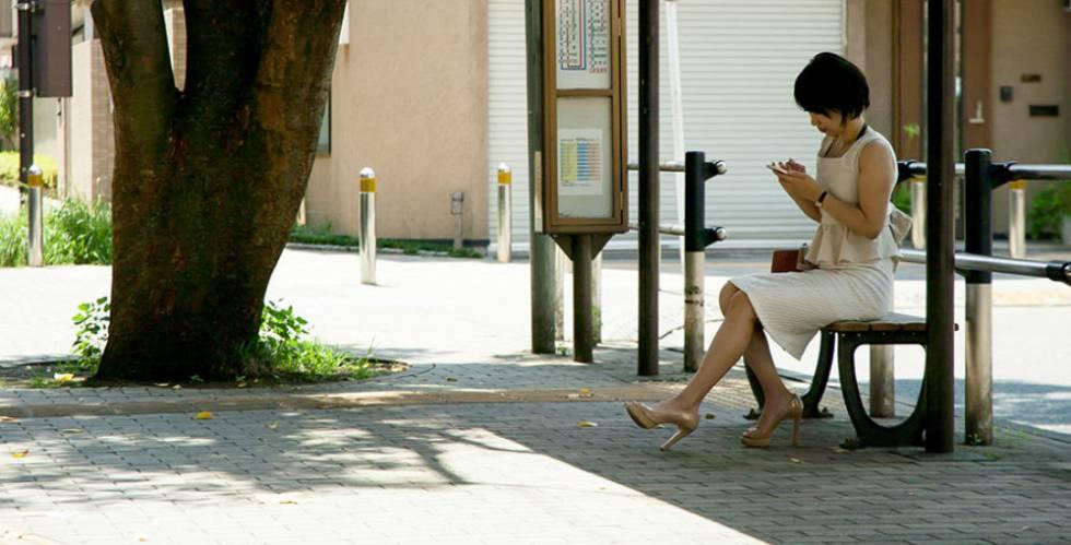 Una mujer espera en una parada de autobús.