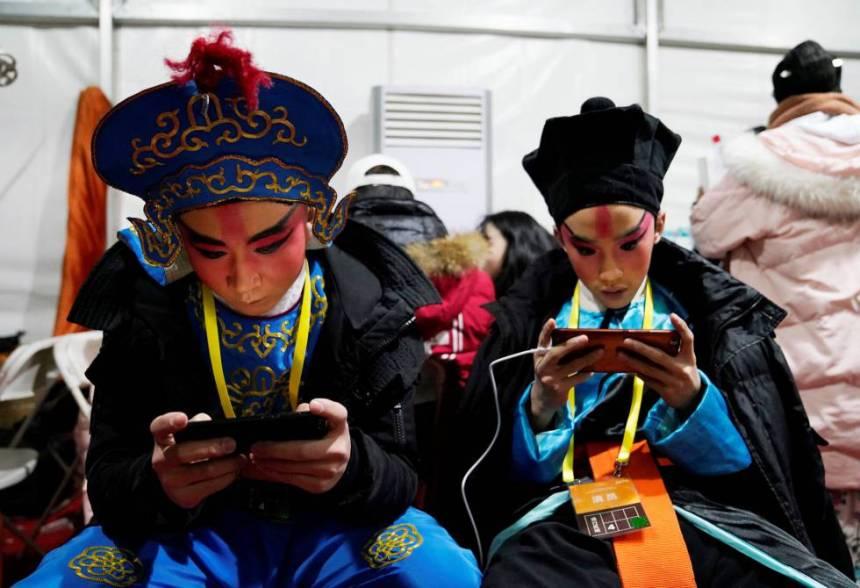 Unos figurantes de la Ópera de Pekín consultan su móvil antes de una función.