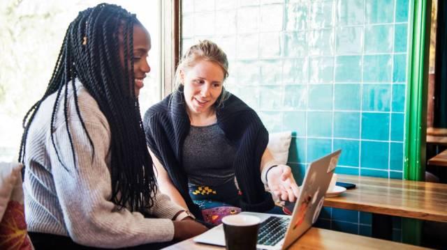 Dos ciudadanas suecas consultan un ordenador en una fotografía del banco de imágenes sueco