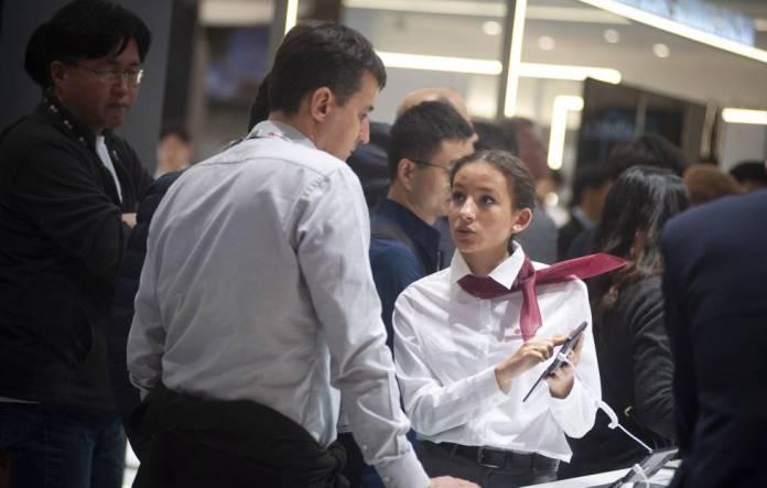 Una azafata muestra un smartphone a asistentes al MWC.
