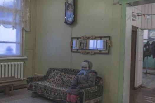 Uma moradora espera sentada dentro de um escritório em Oymyakon.