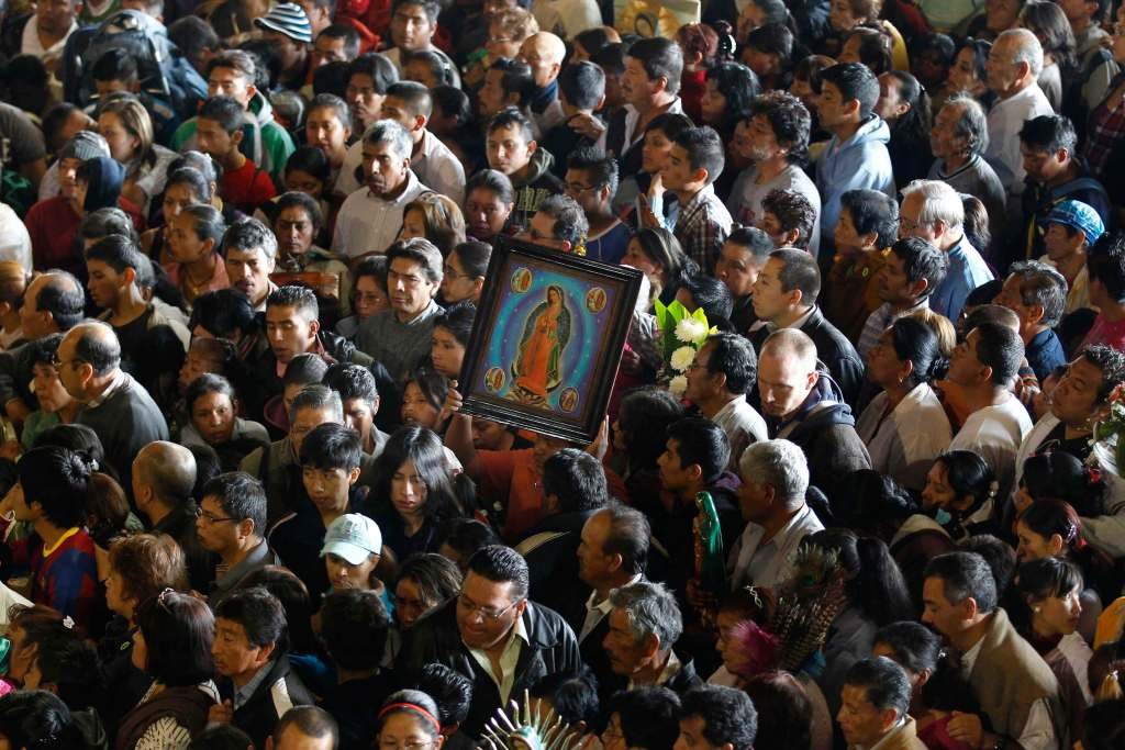 A pilgrim carries an image of Our Lady of Guadalupe in the crowd gathered for the celebration of her feast day in Mexico City Dec. 12. (CNS photo/Edgard Garrido, Reuters) (Dec. 12, 2011)