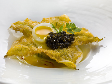 Deep-fried zucchini flower with caviar on shellfish and saffron consommé