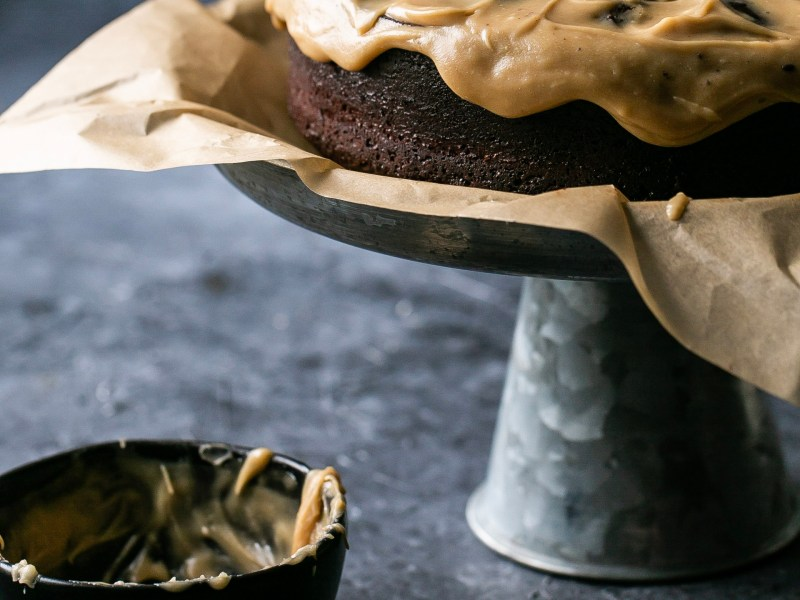 A fininished chocolate cake sits next to an empty bowl of caramel glaze