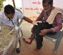 A member of the medical team examines a foot injury.