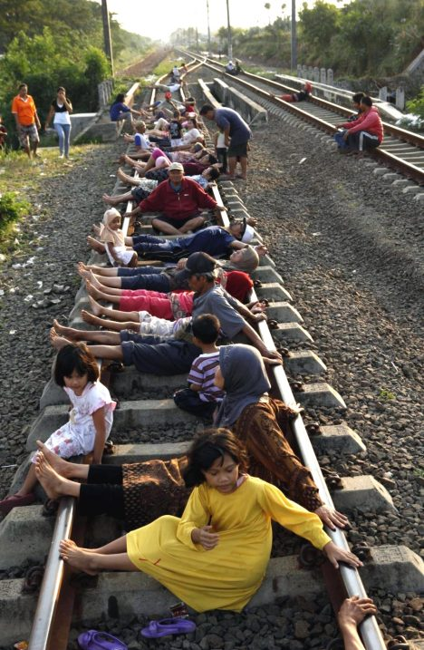 143752-residents-lie-on-railway-tracks-in-rawa-buaya-in-indonesias-west-java-