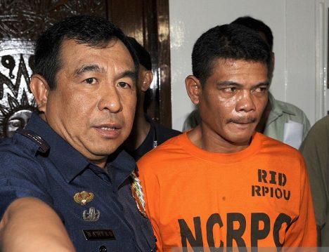 Manilský policejní ředitel Geary Barias (v levo) přivádí vůdce lupičů Ricarda Gomolona.