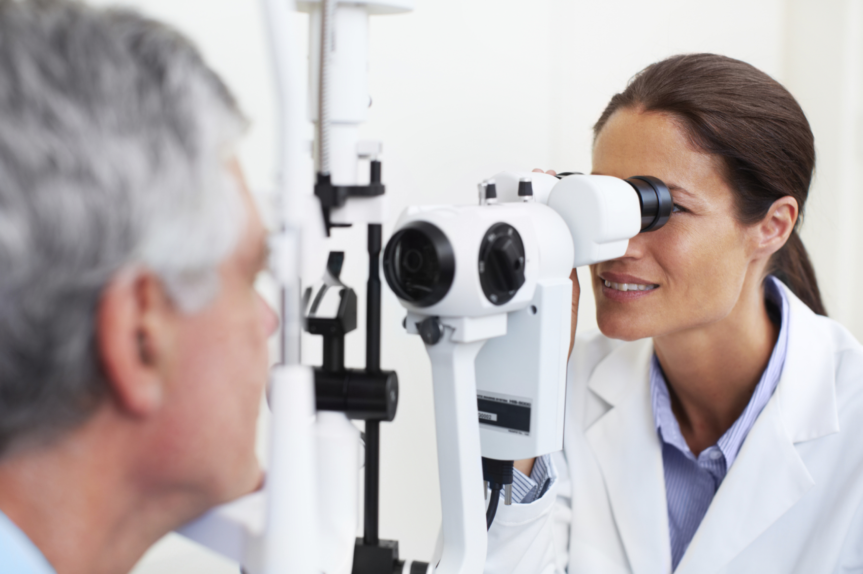 An ophthalmologist examining her patient's eyes with the help of a microbioscope