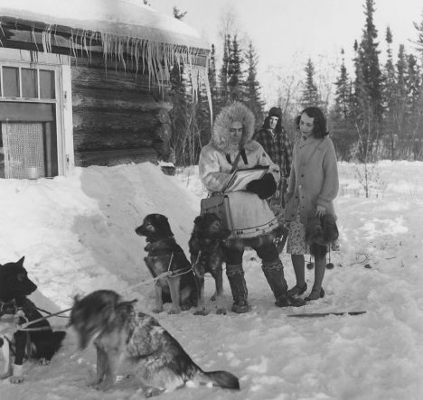 1940s Census taker in Fairbanks, Alaska. He traveled by dog sled to reach this woman's home. The dog musher stands in the background, so he does not overhear the confidential census information.