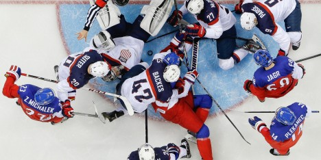 USA goaltender Jonathan Quick looks up form the ice as both Team USA and Team Czech Republic cause a loose puck during the third period of men's quarterfinal hockey game in Shayba Arena at the 2014 Winter Olympics, Wednesday, Feb. 19, 2014, in Sochi, Russia. USA defeated the Czech Republic 5-2. (AP Photo/Matt Slocum)