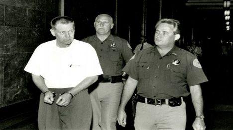Stráže vedou Jamese W. Kinga, podezřelého z loupeže v Wells Fargo Bank.