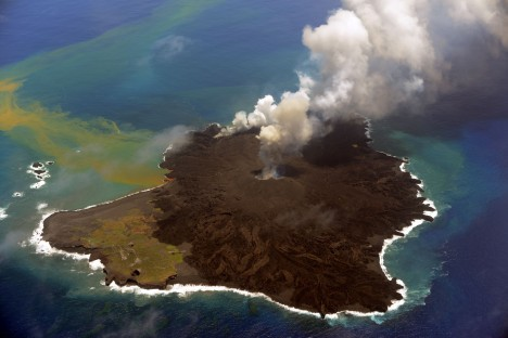 This handout picture taken by Japan Coast Guard on July 23, 2014 shows the newly created islet (R) and Nishinoshima island (L), which are conjoined with erupting lava at the Ogasawara island chain, 1,000 kilometres south of Tokyo. A smouldering islet off Japan's Pacific coast has grown six times in its land surface since before it merged last December with a landmass created by volcanic eruptions. AFP PHOTO / JAPAN COAST GUARD---EDITORS NOTE---HANDOUT RESTRICTED TO EDITORIAL USE - MANDATORY CREDIT